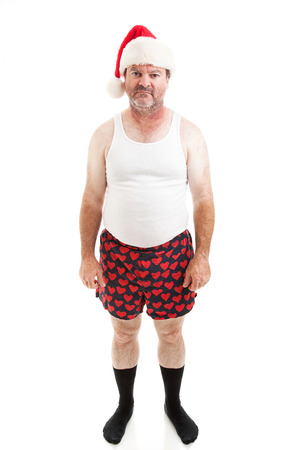 christmas sock: Unhappy, scruffy looking middle-aged man in his underwear, wearing a Santa hat for Christmas and looking upset.  Isolated on white.