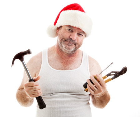 Frustrated dad in a Santa hat holding his tools.  He looks scruffy, like hes been up all night assembling Christmas presents.  Isolated on white.