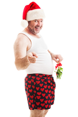 Horny middle-aged man in a santa hat and his underwear, holding mistletoe over his shorts.  Isolated on white.