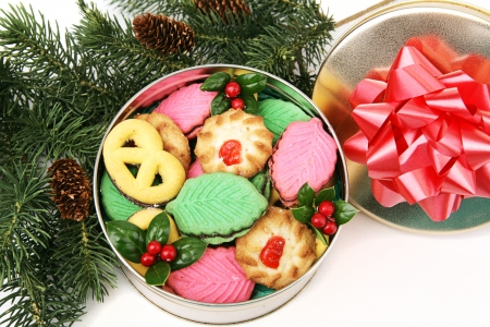 Gift of homemade Christmas cookies in a decorative tin, under the Christmas tree. Stock Photo - 23326306