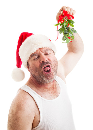 Unshaven middle-aged man in his undershirt, wearing a santa hat and holding mistletoe, waiting for a sloppy wet kiss.  Isolated on white.