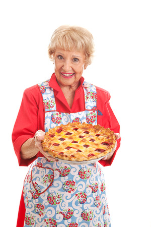 Sweet grandmother holding a delicious homemade cherry pie.  Retro look, isolated on white.   Stockfoto