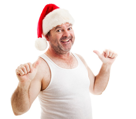 Scruffy unshaven middle-aged man in a santa hat and undershirt, smiling and pointing to himself with two thumbs.  Isolated on white.