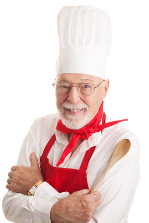 Handsome senior man in a chef's uniform, holding a wooden spoon.  Isolated on white. Stock Photo - 23135281