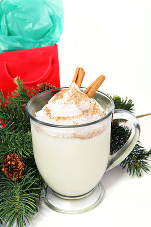 boughs: Mug of delicious Holiday egg nog on white with pine boughs and a Christmas gift.   Stock Photo