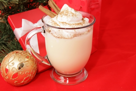 Mug of delicious eggnog, topped with whipped cream, nutmeg, and cinnamon sticks, for Christmas.   Stock Photo - 23326313