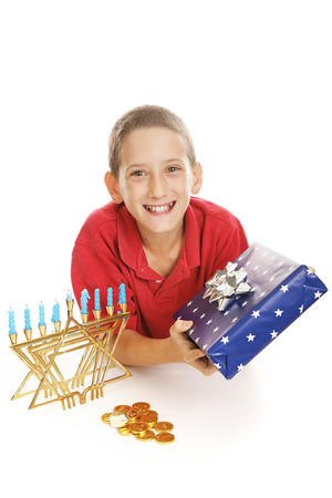 Cute Jewish boy with his Chanukah menorah, gift, and a dreidel and chocolate gelt coins.  White background.   photo
