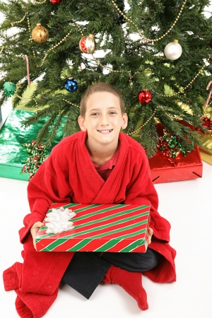 Cute little boy on Christmas morning, eager to open his gifts.