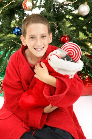 Cute little boy opening his Christmas stocking in front of the tree.