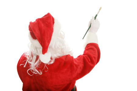 Santa Claus using an artist's paint brush to paint a picture or message.  Isolated design element.   photo