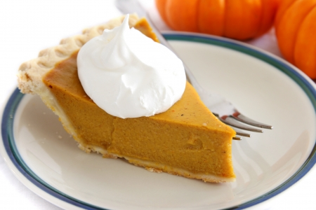 Pumpkin custard pie slice with whipped cream topping.   photo