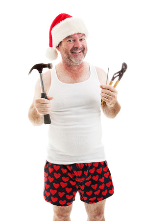 Lachende vader in een kerstmuts, met zijn gereedschap. Hij is klaar om kerstcadeaus te monteren.