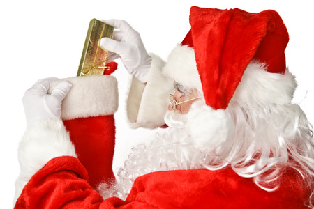 christmas costume: Santa Clause putting a shiny Christmas present into a stocking.  Isolated on white.   Stock Photo