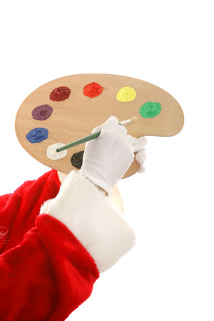 Santa's hands holding a paint palette and a paintbrush.  Isolated design element.  photo