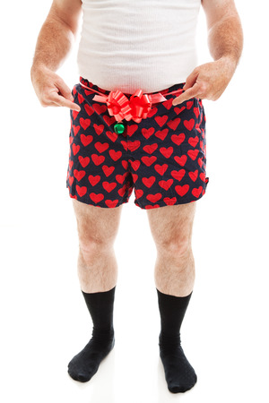 Humorous photo of a guy in boxer shorts with a bow, offering his crotch as a Christmas gift.  Isolated on white.