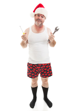 Frustrated dad in a Santa hat holding his tools.  He looks scruffy, like hes been up all night assembling Christmas presents.  Full body isolated on white.