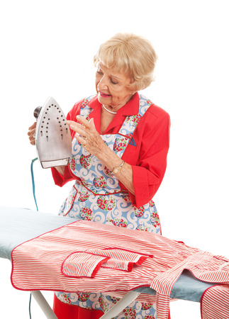 Pretty senior woman testing her iron to see if it is hot.  Isolated on white.