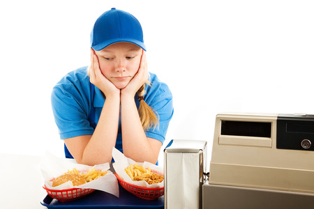 Unhappy teenage girl has a boring job serving fast food.  Isolated on white.