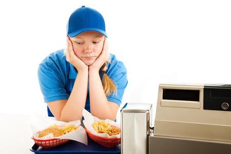 occupation: Ongelukkig tienermeisje heeft een saaie baan serveren fast food. Geïsoleerd op wit. Stockfoto