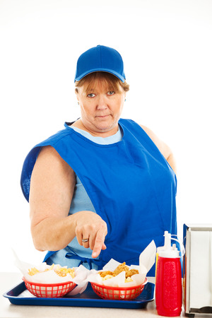 Unfriendly, no-nonsense cashier at a fast food restaurant, serving your order.  Isolated on white.   Stock Photo