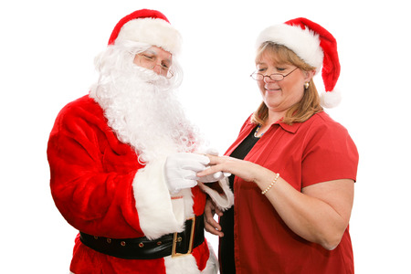 Santa Clause giving his wife a beautiful diamond ring for Christmas.  Isolated on white.   photo