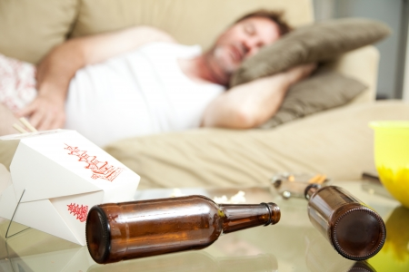 Man passed out on his couch in his underwear.  A full ashtray, empty beer bottles and empty Chinese take out container scattered on his coffee table.   photo