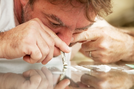 snort: Middle-aged man using a rolled up dollar bill to snort cocaine off a glass coffee table.  **Dramatization - no illegal drugs were used in the creation of this photo** Stock Photo
