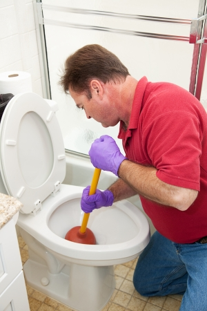 Man wearing rubber gloves and using a plunger to unclog the toilet.   Archivio Fotografico