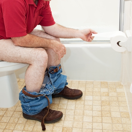 bowel movement: Man sitting in the bathroom on the toilet, pulling off a piece of toilet paper.