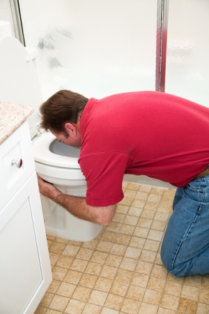 Man kneeling down in the bathroom, vomiting into the toilet.   photo