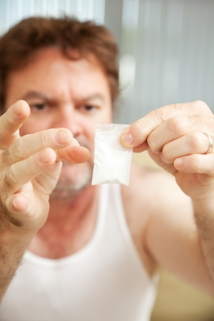 snort: Drug addict holding a gram of cocaine.  **Dramatization - no illegal drugs were used in the making of this photograph**