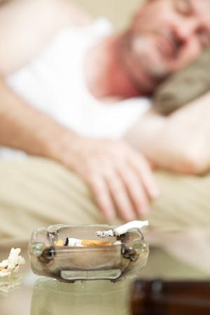 wifebeater: Posacenere con un giunto di marijuana che brucia in primo piano, con un uomo addormentato in background. Profondit� di campo. ** Drammatizzazione - droghe illegali sono stati utilizzati per la realizzazione di questa fotografia **