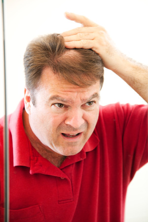 Man in his forties looking in the mirror discovers a bald spot in his hair.   photo