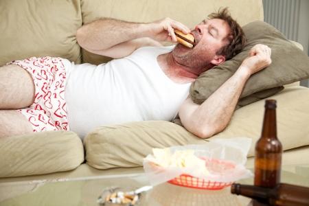 Chômeurs homme d'âge moyen à la maison sur le canapé dans ses sous-vêtements, de manger un hamburger, avec un Joing de la marijuana dans les bouteilles de bière et cendrier qui traînent.