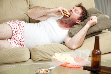 joblessness: Unemployed middle aged man at home on the couch in his underwear, eating a hamburger,  with a marijuana joing in the ashtray and beer bottles lying around.