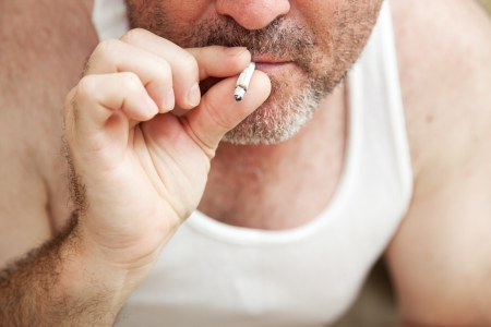 wifebeater: Closeup view of a man smoking a marijuana joint.  **Dramatization - no illegal narcotics were used in the making of this photograph**