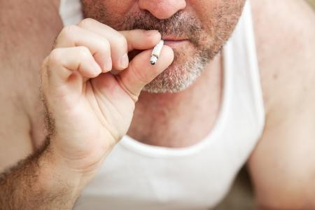 wifebeater: Closeup vista di un uomo di fumare uno spinello di marijuana. ** Drammatizzazione - non narcotici illegali sono stati utilizzati per la realizzazione di questa fotografia **