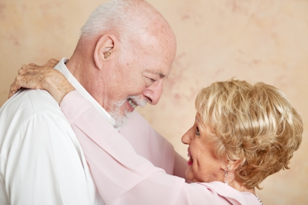 Senior couple in a romantic embrace, looking deep into each others eyes.   photo