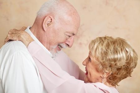 Senior joven en un abrazo romántico, mirando profundamente a los ojos del otro. Foto de archivo - 23950287