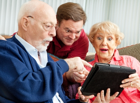 Adult son enjoys showing his parents how to use the new Tablet PC he gave them as a holiday gift. Stock Photo - 23950288