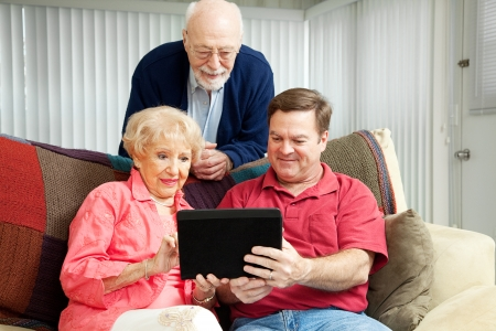 Adult son teaching his parents to use their new tablet pc.   photo