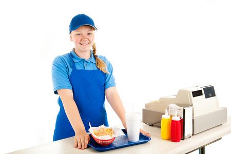 フレンドリーで笑顔 10 代のキャッシャーはファーストフードのレストランで提供します。白で隔離されます。