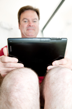 Man using his tablet pc while sitting in the bathroom on the toilet.   photo