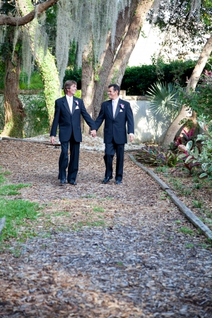 Handsome gay wedding couple walking together on the garden path, symbolizing the walk through life.   photo