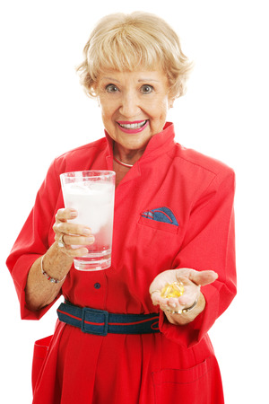 inflamation: Healthy senior woman taking omega 3 fish oil supplements with a glass of ice water.  Isolated on white.