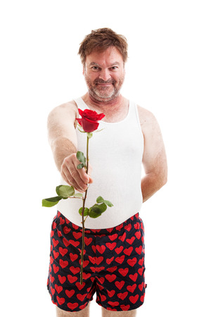 Scruffy looking guy in his underwear handing you a single red rose.  Isolated on white. photo