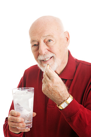 inflamation: Portrait of a healthy senior man taking omega 3 fish oil with a glass of ice water.  White background.