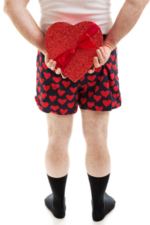 Man in heart underwear holding a box of Valentines Day candy behind his back.  Isolated on white.