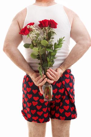 wifebeater: Vista posteriore di uomo in boxer cuore in possesso di un mazzo di fiori dietro la schiena. Sfondo bianco.