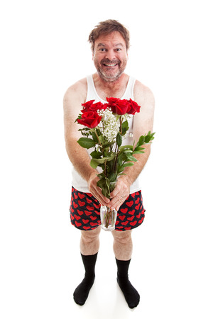 unattractive: Humorous photo of a scruffy looking middle aged man in his underwear holding a bouquet of roses for his sweetie.  Full body isolated on white.